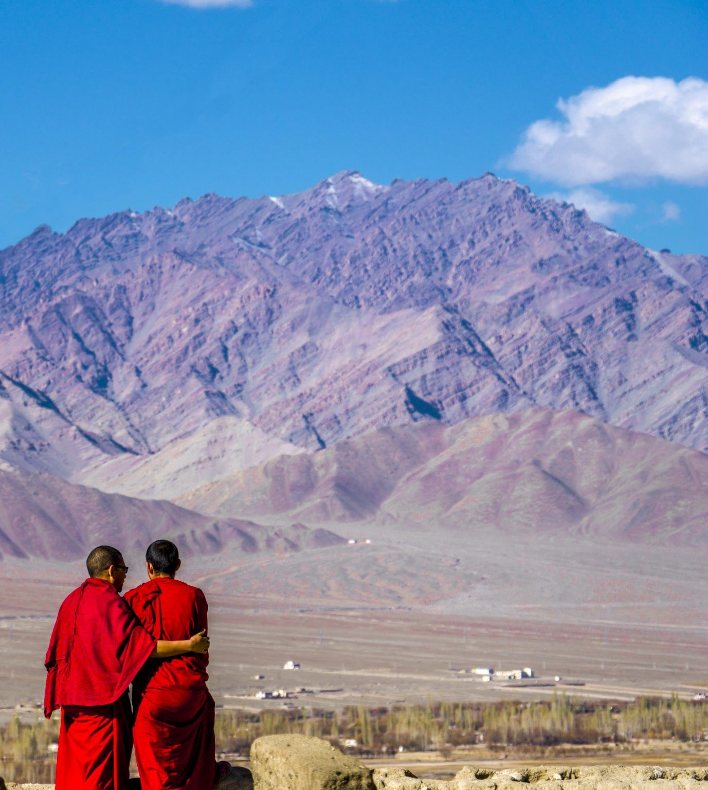A photograph of two people wearing red material looking out towards the mountains on a sunny day.