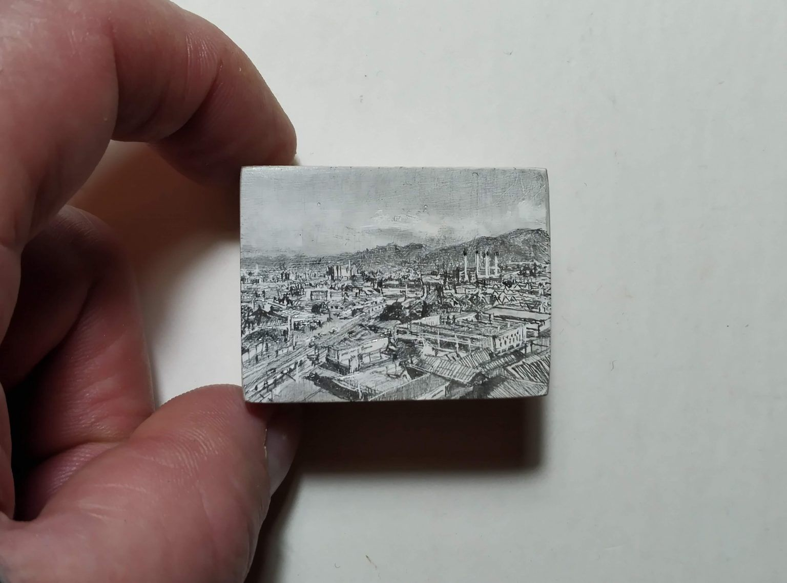 Finger and Thumb holding a tiny B&W drawing of a city scape.