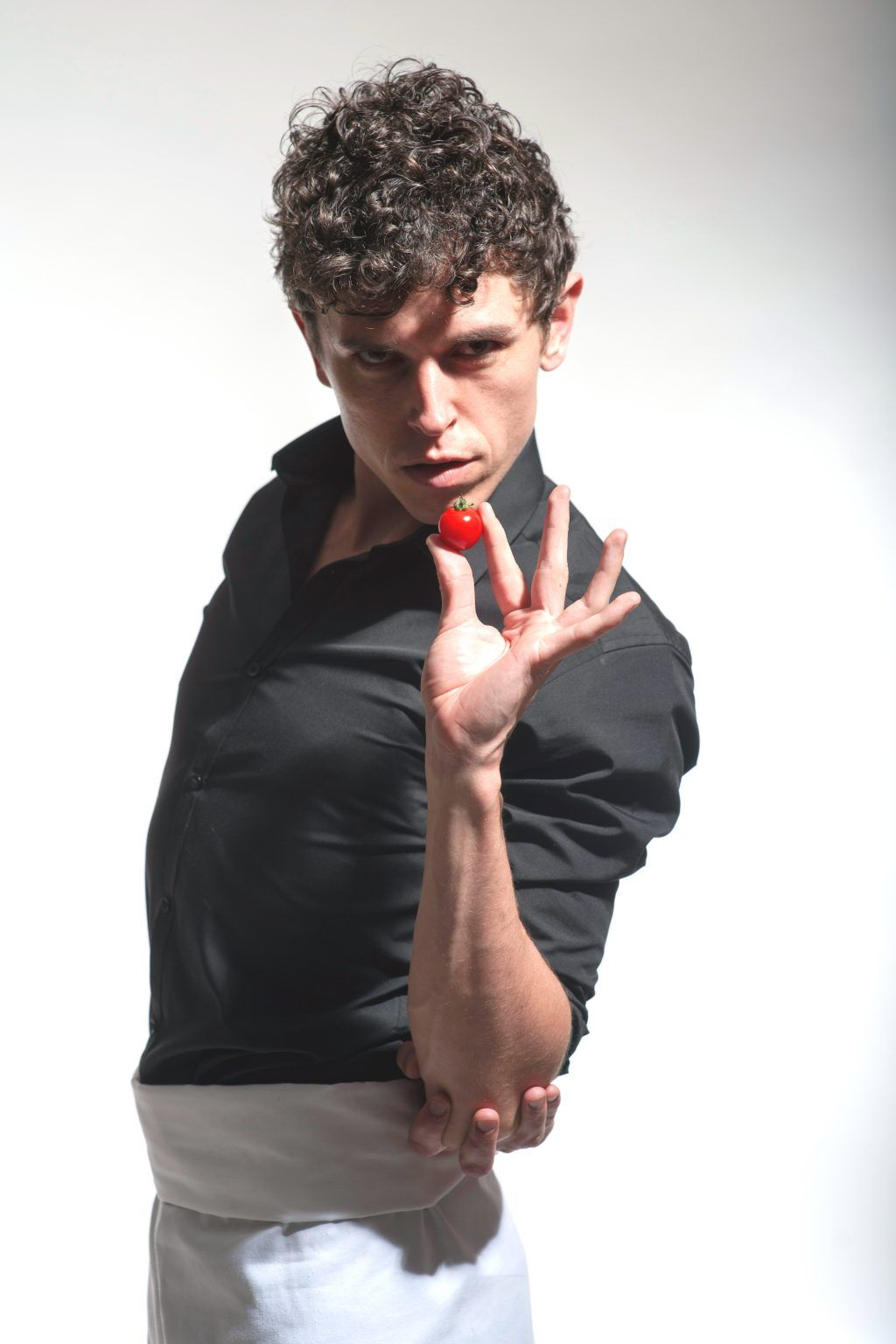 Portrait Photo of a Waiter holding one cherry tomato between finger and thumb